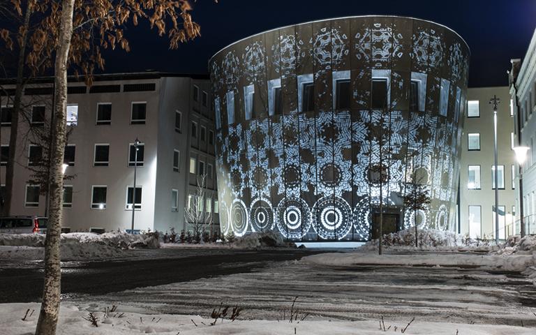 Bild på verket Blomman från Weena en fasad. Ljuset lyser igenom fasaden.