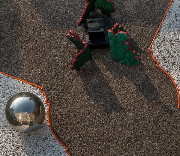 Grus i olika färger separerade av röda kanter och skulpturer.