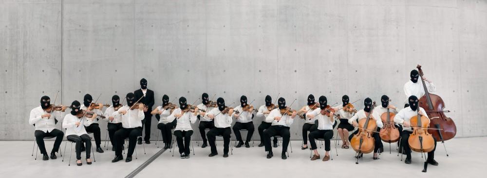 En tjugo personer stark stråkorkester med fioler, viola och cello. Alla musiker har vita skjortor och svarta rånarluvor. Orkestern sitter och spelar i ett kalt rum av betong. Sislej Xhafa, Again and Again