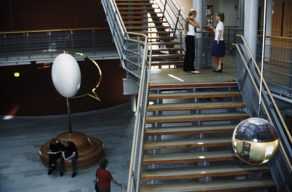 """Verket """"Tanke Inkognito"""" kan ses som en korsning mellan en vit jordglob och en tom pratbubbla. Några studenter sitter och samtalar på träsockeln som är en sittbänk. Mats Bigert och Lars Bergström, Tanke inkognito/Rum för reflexion"""