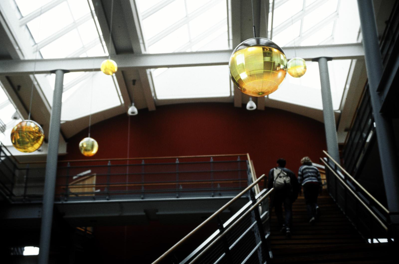 Två stora och tre små gula och upplysta globarmaturer hänger på olika höjd i entréhallens tak. Mats Bigert och Lars Bergström, Tanke inkognito/Rum för reflexion