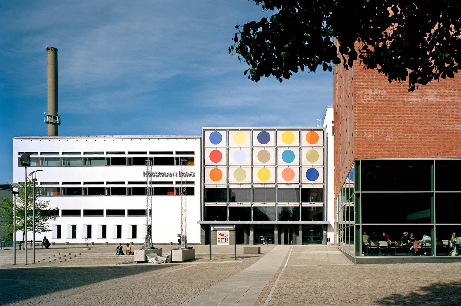 Högskolan i Borås utifrån. Ena flygeln av tegel, den andra vit. I mitten biblioteksbyggnaden med solavskärmningen halvvägs nerfälld och de olikfärgade prickarna väl synliga. Kontrapunkt, Eva Stephenson-Möller