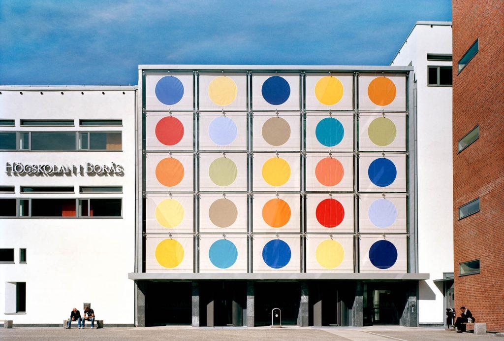 Biblioteksbyggnaden utifrån med solavskärmningen helt nedfälld. De tjugofem stora olikfärgade prickarna syns tydligt. Kontrapunkt, Eva Stephenson-Möller