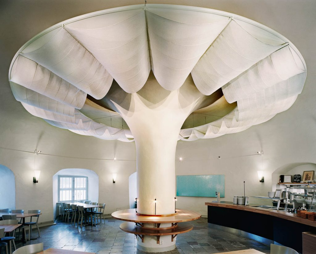 Himlavalv. Textila våder i tunna längder och olika nyanser av vitt har draperats kring toppen av rummets mittpelare. Verkets form för tanken till en blomma eller ett svampmoln. Nomura Kazuyo, Reflektion. Himlavalv, Reflex 1 och 2