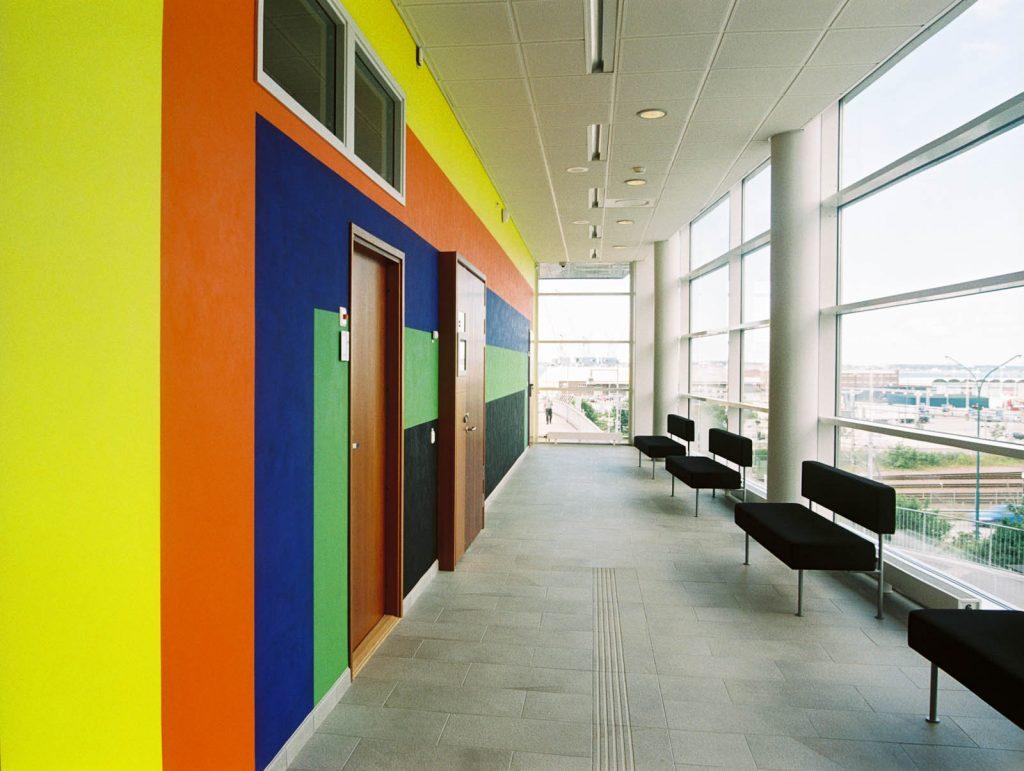 Korridor på första våningen. Ena väggen utgör en del av verket med breda horisontella och vertikala linjer i starka färger. Andra väggen är av glas. Ann Edholm, Transire