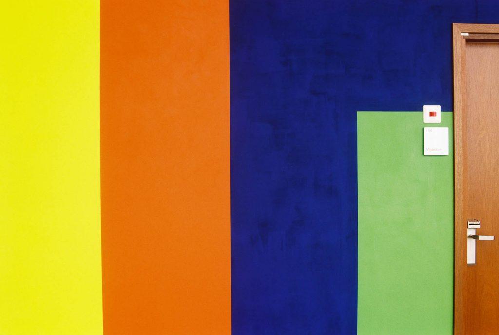 Detalj. Breda vertikala färgpartier i orange, blått och grönt, i anslutning till en brun dörr. Ann Edholm, Transire