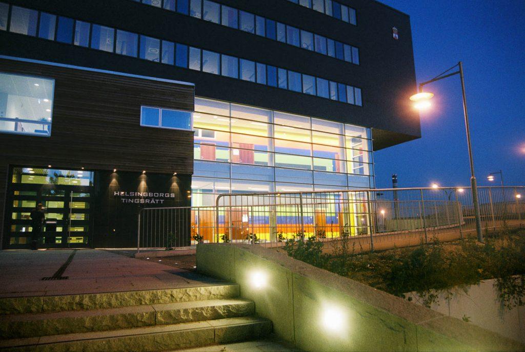 Tingshuset utifrån i kvällsmörker. Genom glaspartiet syns den upplysta väggmålningen som täcker två våningsplan. Ann Edholm, Transire