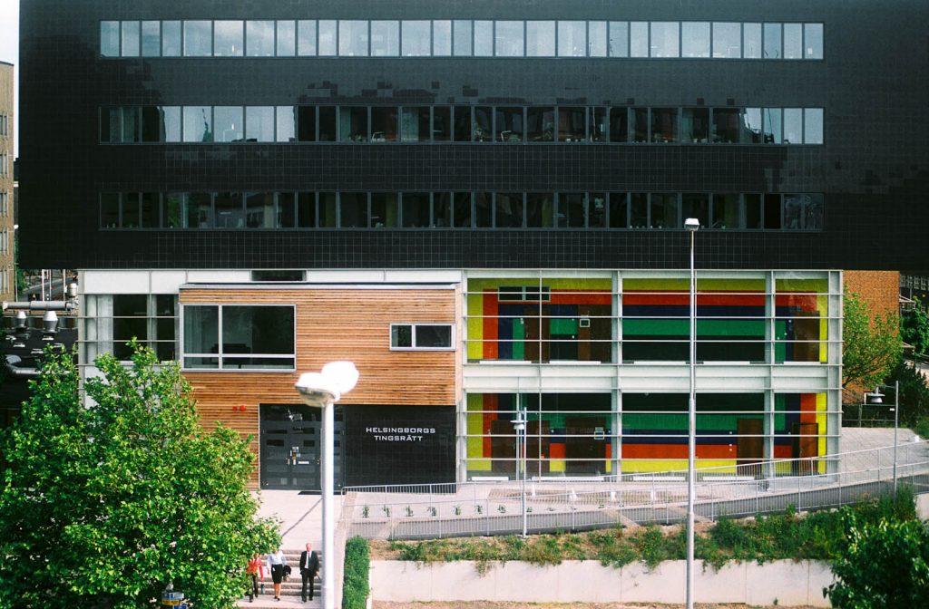 Tingsrätten utifrån. Övervåningarna är svarta. Genom glaspartiet på de två första våningarna syns väggmålningens tydliga färgpartier. Ann Edholm, Transire