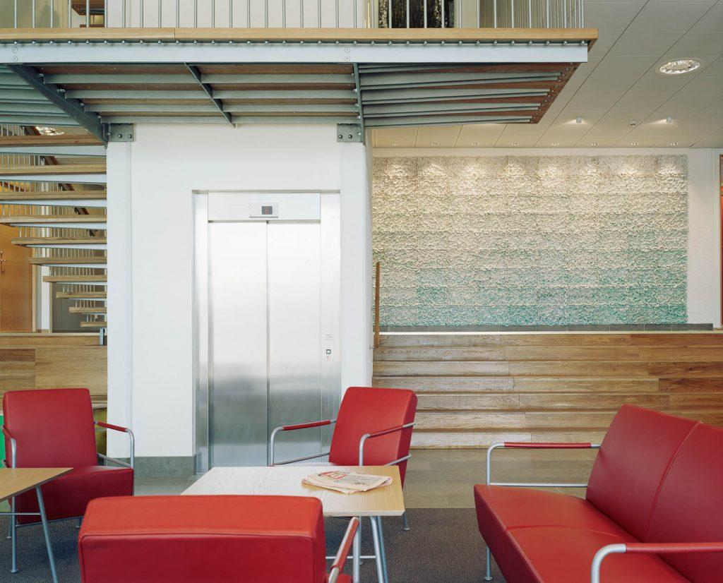Hiss och röda stolar. I bakgrunden väggen med keramikplattor. Renata Francescon, Fruset šögonblick
