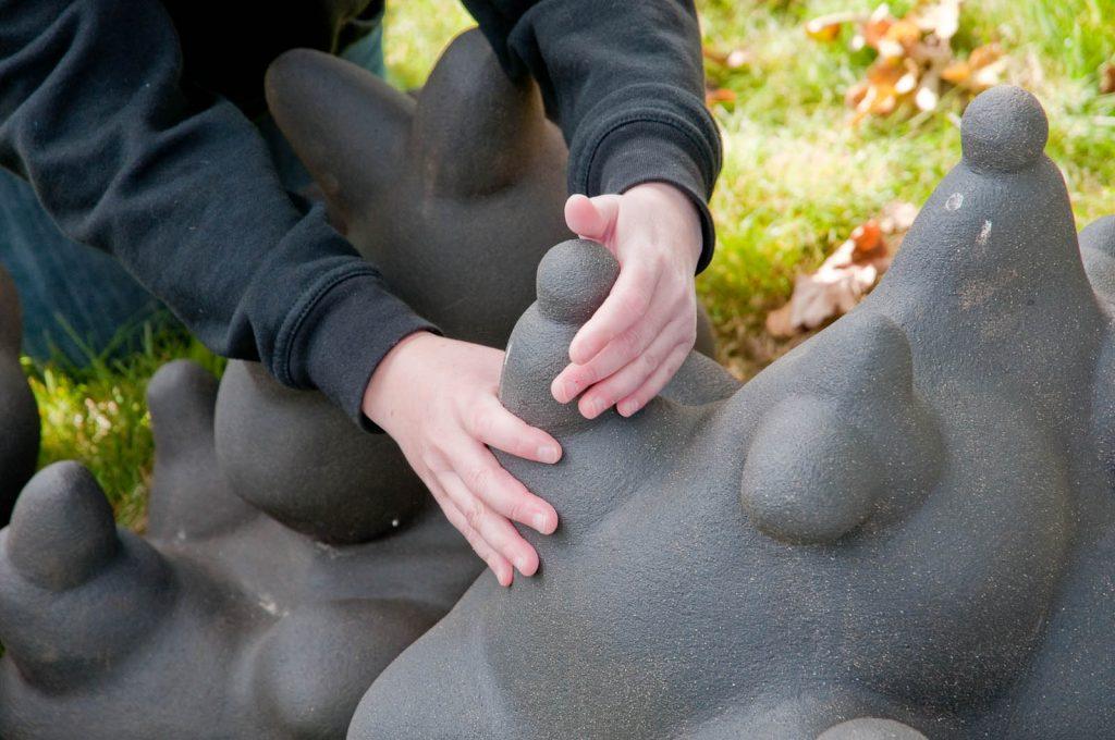 """De små """"bergsfigurerna"""" i svart lera är spännande att känna på. Detalj med barnhänder. Jennifer Forsberg, En liten berättelse i tre delar - Den Eken och molnet"""