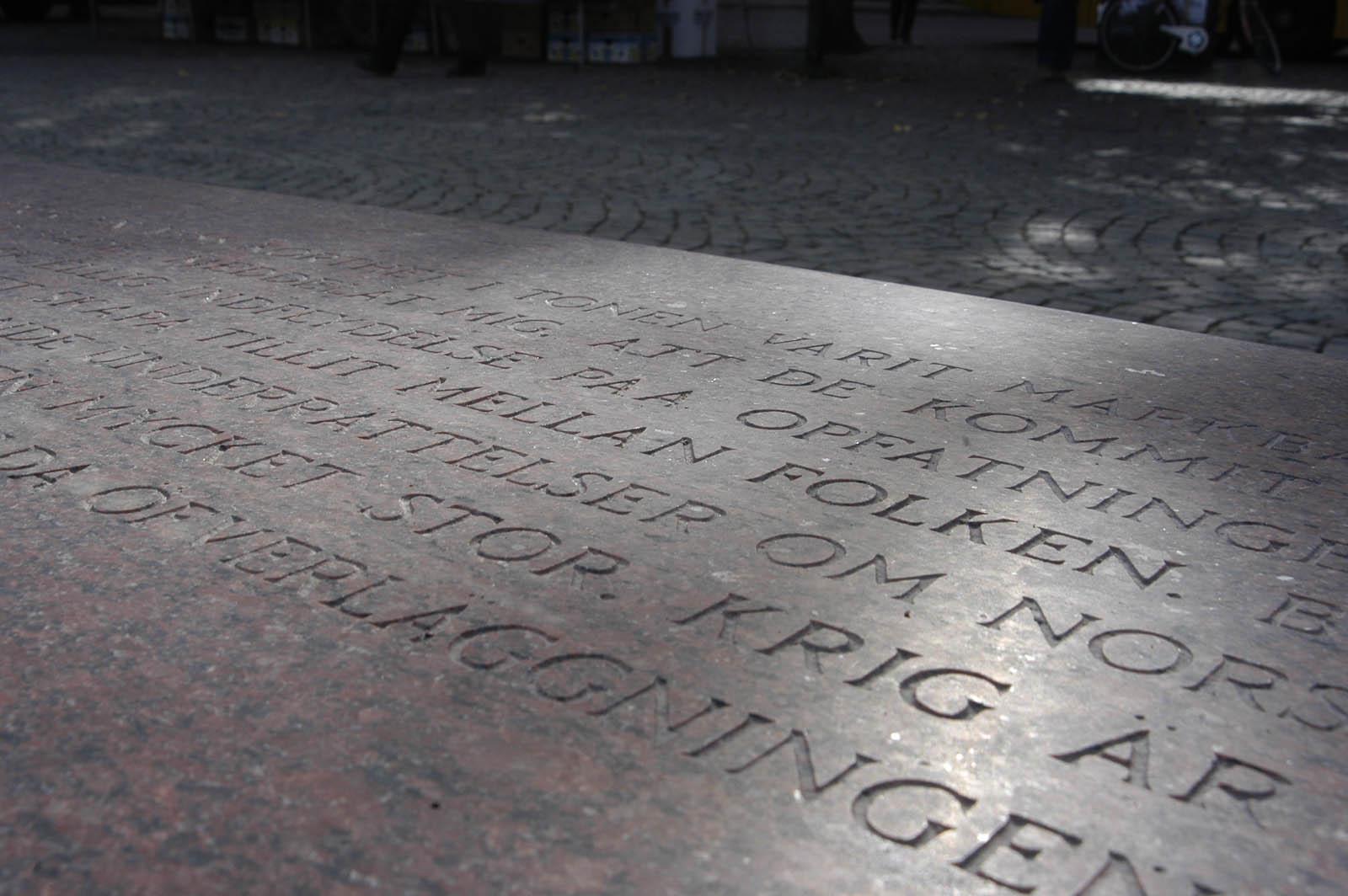 """Del av graverad text på granitbänk. Man anar orden: """"folket"""" och """"krig.""""Jenny Holzer, For Karlstad."""