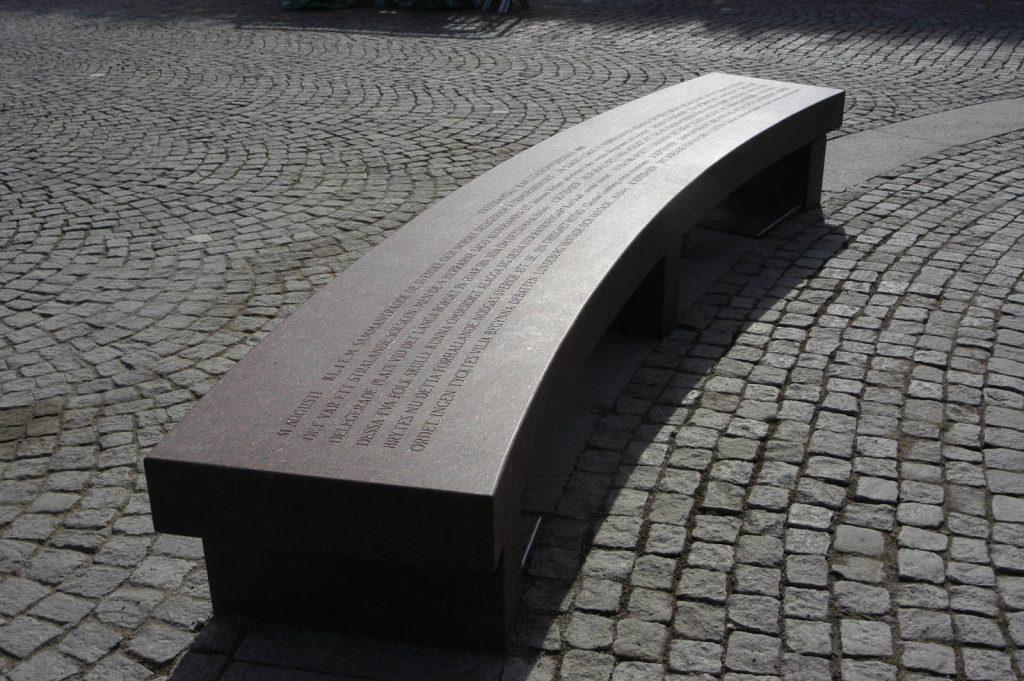 Välvd röd granitbänk med graverad text längs hela sittytan, stående på kullerstenar. Jenny Holzer, For Karlstad.