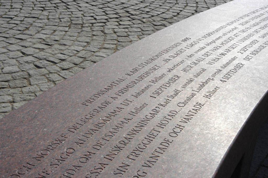 """Del av gravyr på bänk. Högst upp på bänken står det: """"Fredssamtal: Karlstadskonferensen 1905."""" Jenny Holzer, For Karlstad."""
