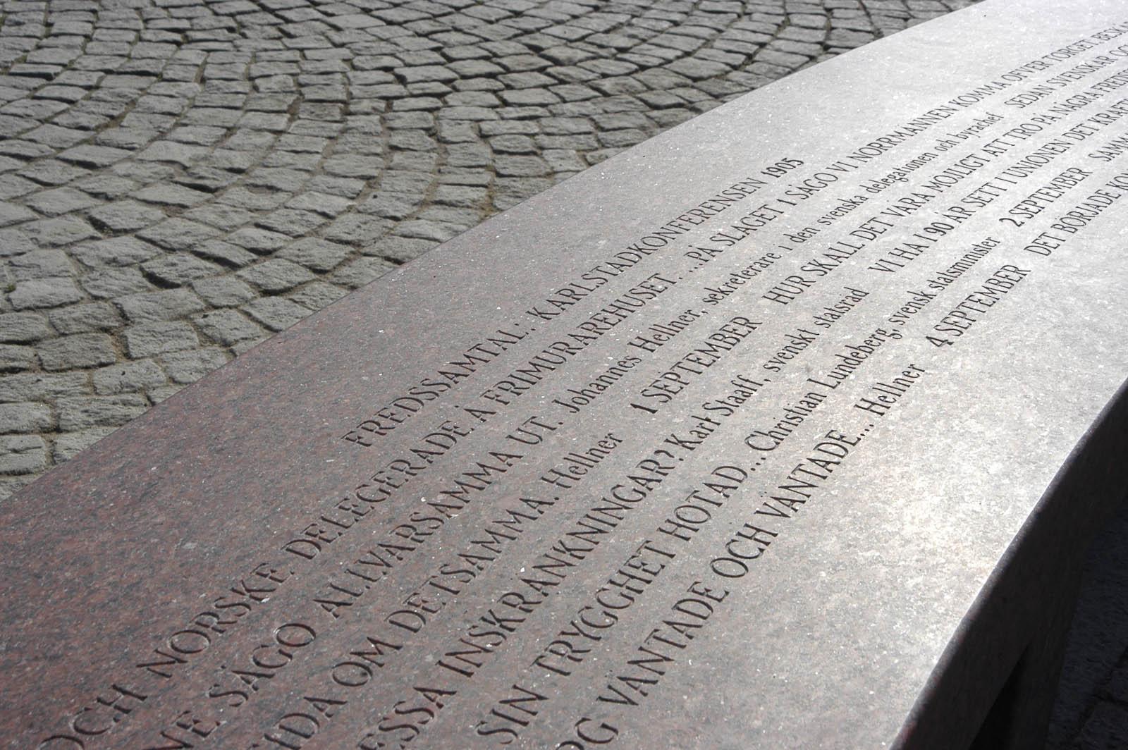 Del av gravyr på bänk. Högst upp på bänken står det: Fredssamtal: Karlstadskonferensen 1905. Konstverk av Jenny Holzer, For Karlstad.