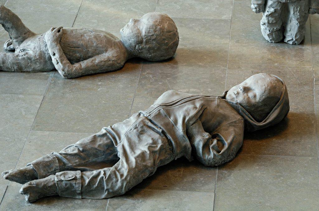 Ett av de liggande barnen har för stora upprullade jeans och munkjacka. Ett annat barn har inga kläder alls. Båda ser ofärdiga, liksom oavslutade ut. Under av Charlotte Gyllenhammar
