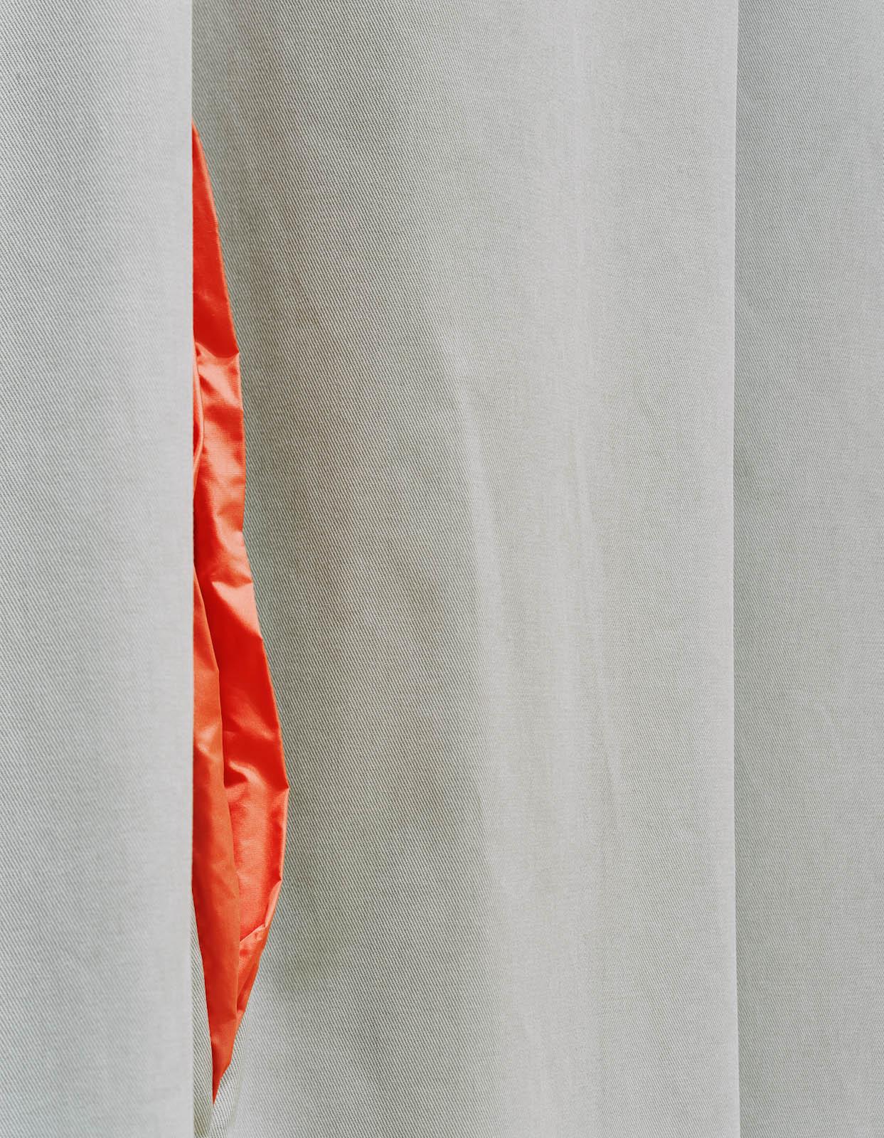 Detalj. Ur en slits i det grå tränger rött tyg fram, som ett par läppar. Kajsa G Eriksson, Ridån