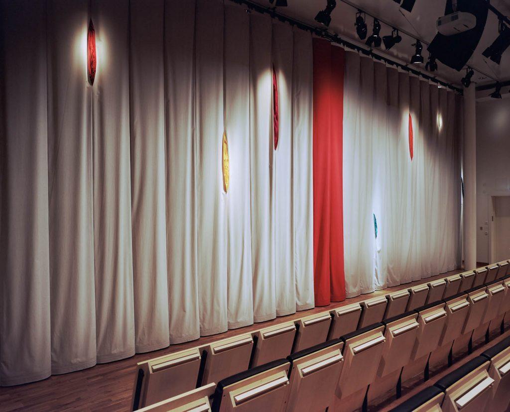 Fördragen ridå framför rader av stolar. Mittfåran markeras av röda längder. I det grå tyget finns flera skåror där färgglatt tyg sticker fram. Kajsa G Eriksson, RidŒån