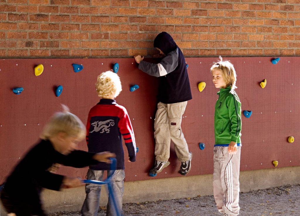 Barn leker på den låga klätterväggen. Love and devotion, helhetsgestaltning av Olaus Petri-skolan