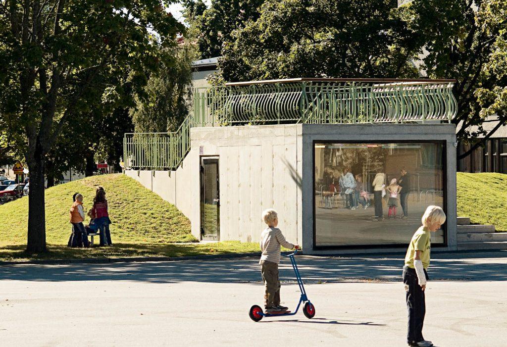 En betongkub har bäddats in i en kulle på skolgården, med ett välvt grönt staket på taket. Love and devotion, helhetsgestaltning av Olaus Petri-skolan