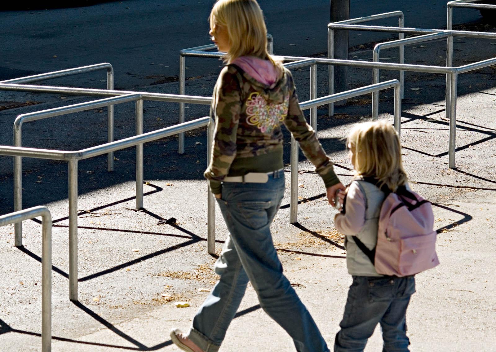 En vuxen och ett barn passerar metallräcket som inhägnar skolgården. Love and devotion, helhetsgestaltning av Olaus Petri-skolan