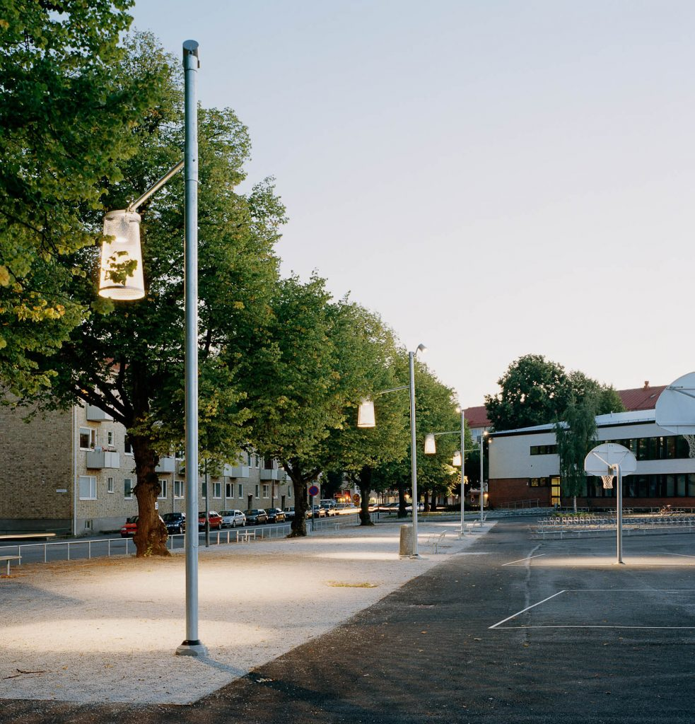 Boulebanan belyses av gatlyktor med stora lampskärmar som påminner om läslampor. Love and devotion, helhetsgestaltning av Olaus Petri-skolan