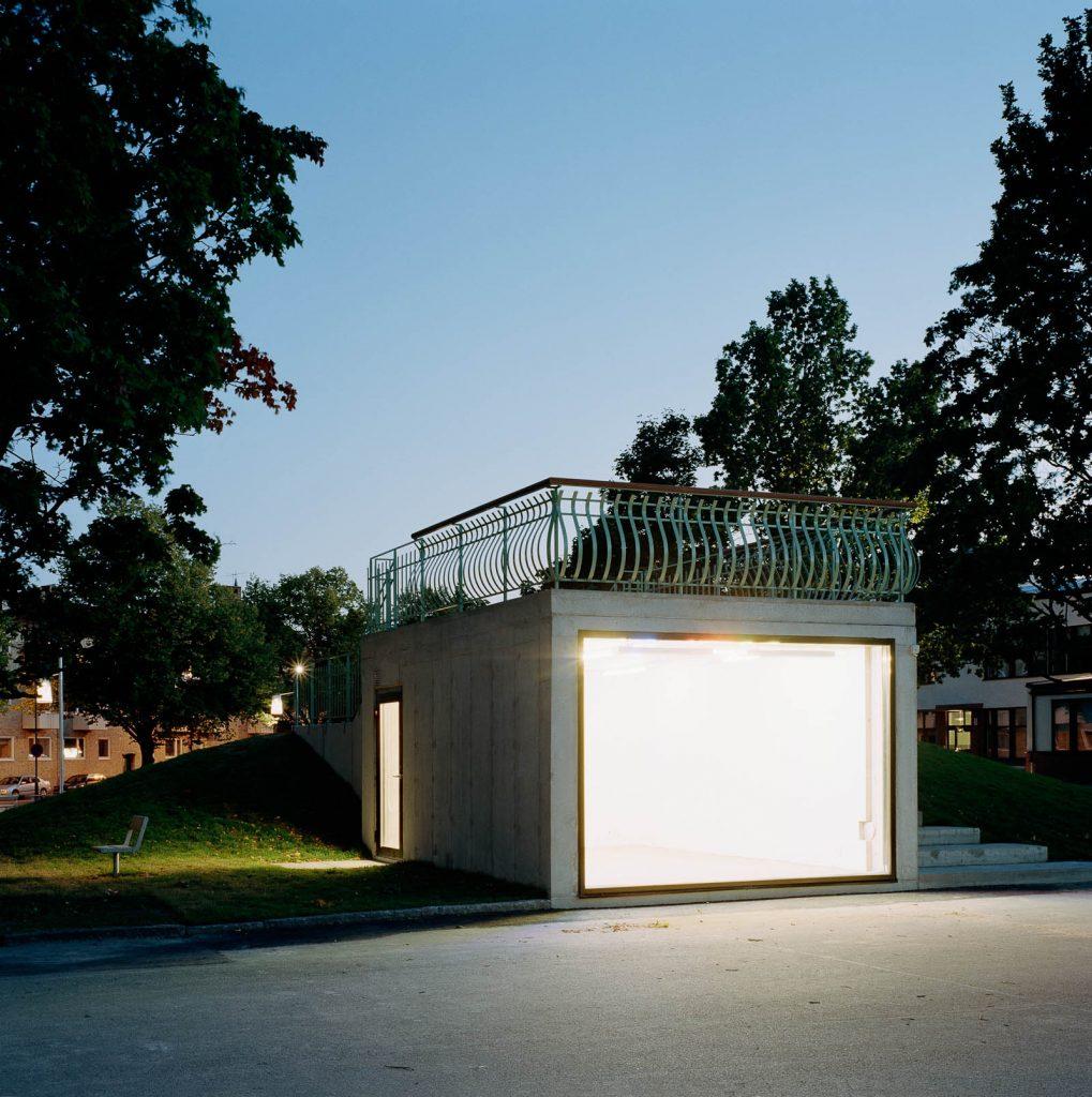 Nattetid strålar det om betongkubens glasvägg när den är upplyst inifrån. Love and devotion, helhetsgestaltning av Olaus Petri-skolan
