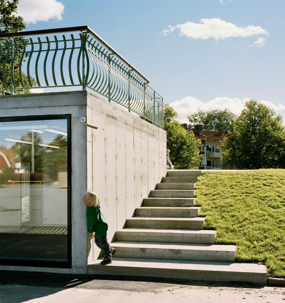 Bredvid betongkuben går en trappa upp på kullen och till kubens tak. Love and devotion, helhetsgestaltning av Olaus Petri-skolan
