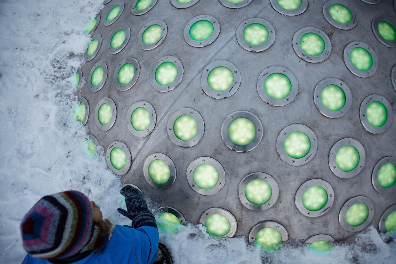 Ett barn undersöker en stålkupol som sticker upp ur snön täckt av gröna lysande lampor. Markus Lantto, Termonoder