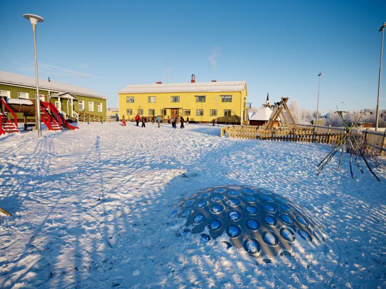 En grön och en gul skolbyggnad i skarp vintersol. På lekplatsen faller skuggorna långa över termonoden. Markus Lantto, Termonoder, 2009