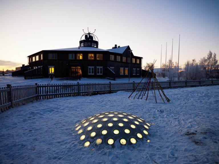 Termonodens lampor lyser gula på den mörka skolgården. I bakgrunden en upplyst byggnad. Markus Lantto, Termonoder, 2009