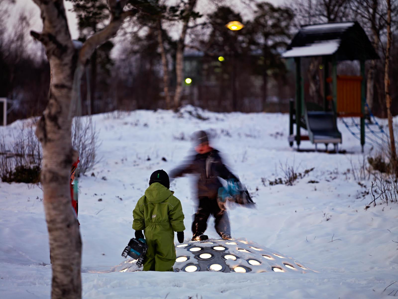 Två barn leker på stålkupolen som sticker upp ur snön. Lamporna lyser vita. I bakgrunden en lekplats. Markus Lantto, Termonoder, 2009