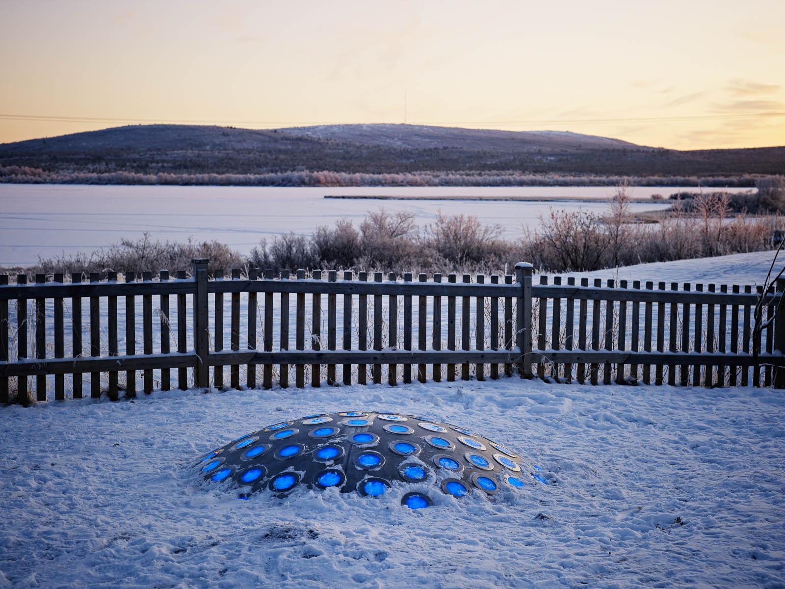Termonodens lampor lyser blå i den snötäckta gryningen. Bakom staketet sträcker sig fjället. Markus Lantto, Termonoder, 2009
