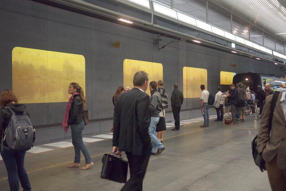 Människor väntar på tåget som kör in vid perrongen. På väggen projektioner av vatten och träd i dis. Tania Ruiz Gutiérrez, Annorstädes