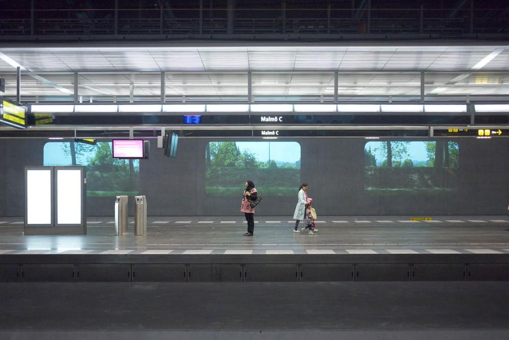 Två personer på en tågperrong. I bakgrunden tre projektioner av bilder med grönska, träd och en låg mur. Tania Ruiz Gutiérrez, Annorstädes