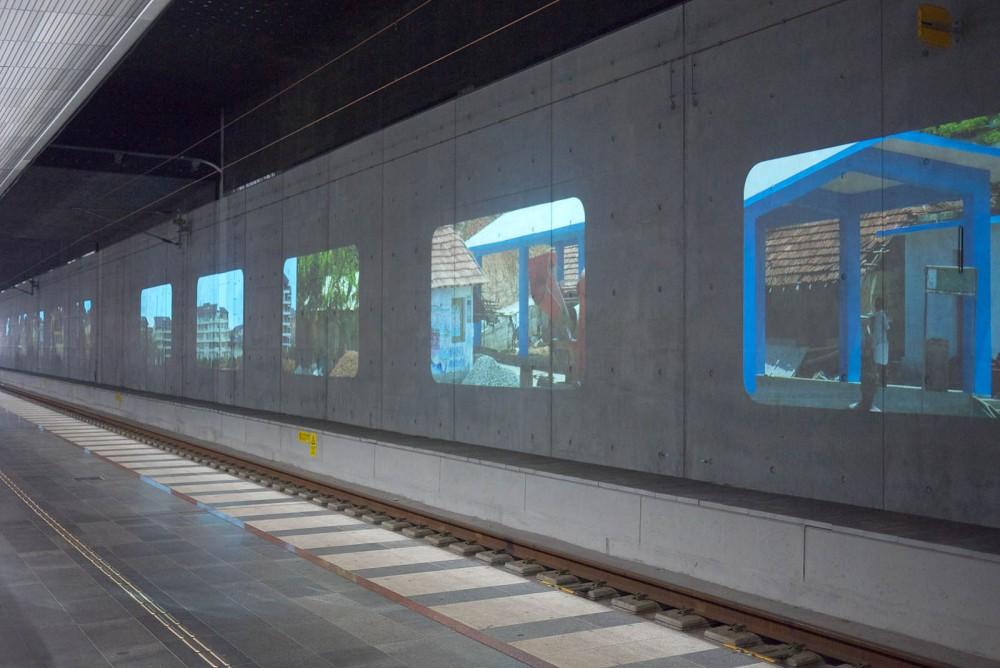 På betongväggen bakom en tågräls syns flera projektioner av bilder med hus på. Tania Ruiz Gutiérrez, Annorstädes