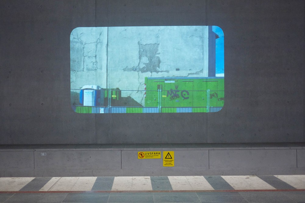 Projektion av bild på grön container vid en betongvägg. Tania Ruiz Gutiérrez, Annorstädes