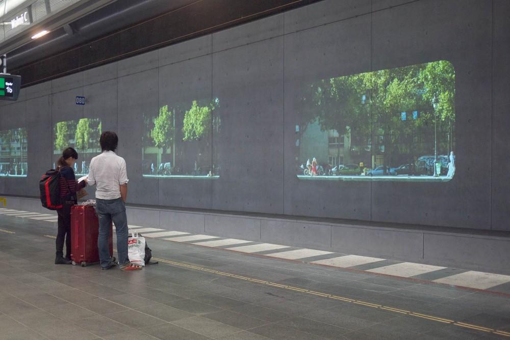 Två personer med packning väntar på perrongen och tittar på projektioner av stadsmiljöer. Tania Ruiz Gutiérrez, Annorstädes