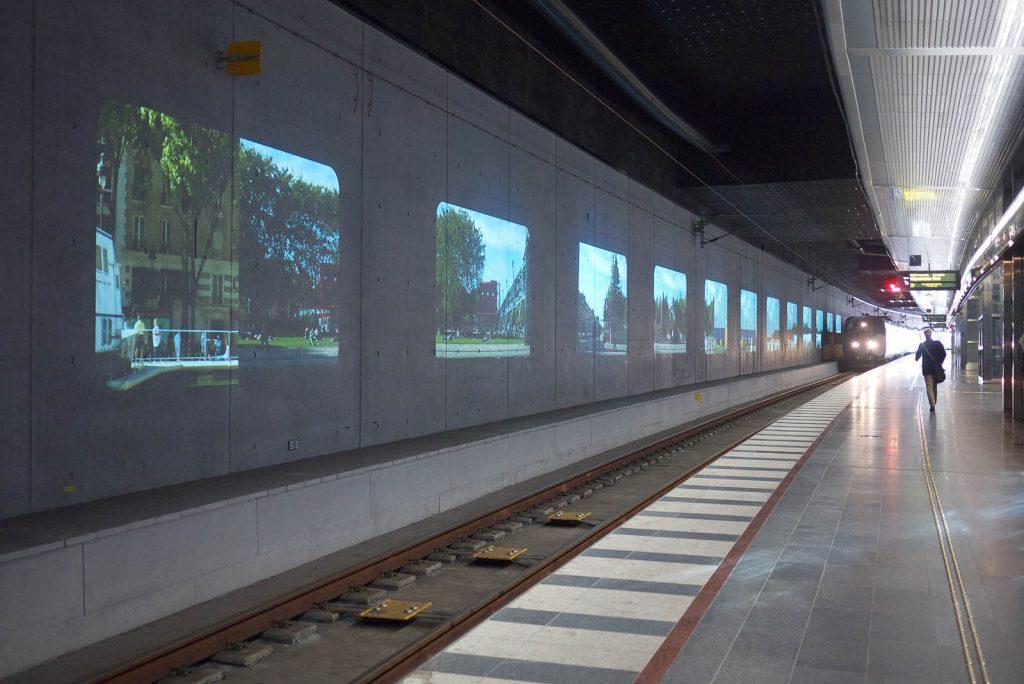Ett tåg kör in på perrongen. På väggen projektioner av hus och träd. Tania Ruiz Gutiérrez, Annorstädes