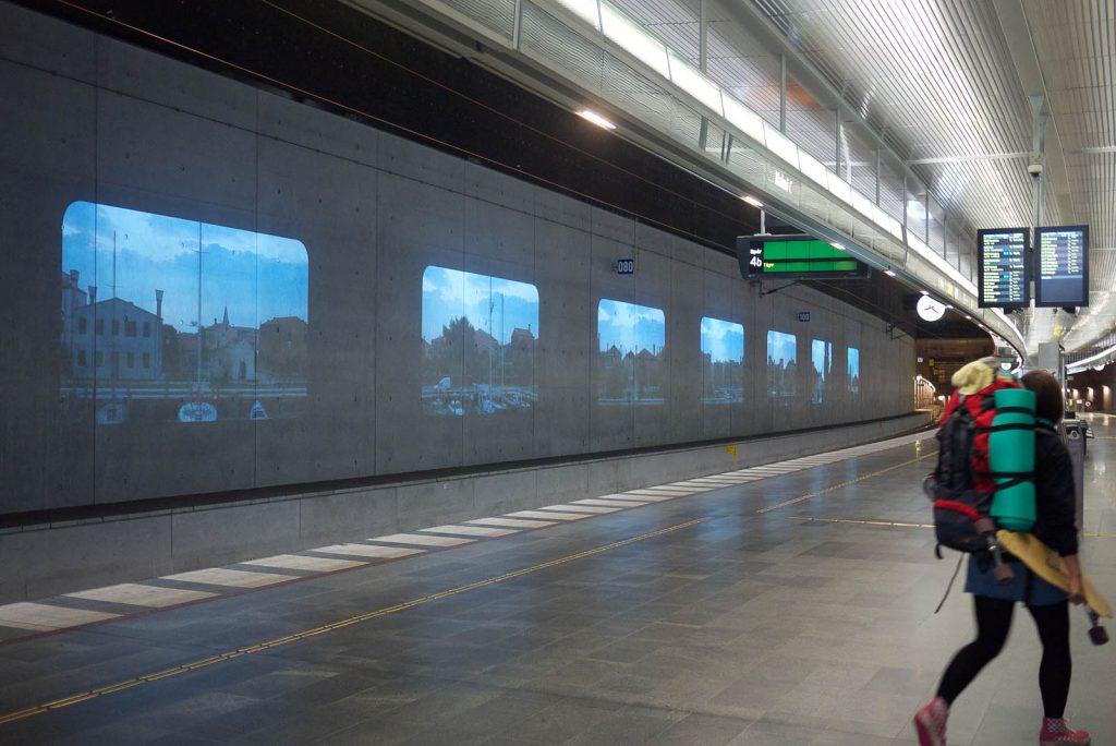 En rad projektioner längs perrongväggen, bilderna tycks vara tagna i en stad. Tania Ruiz Gutiérrez, Annorstädes
