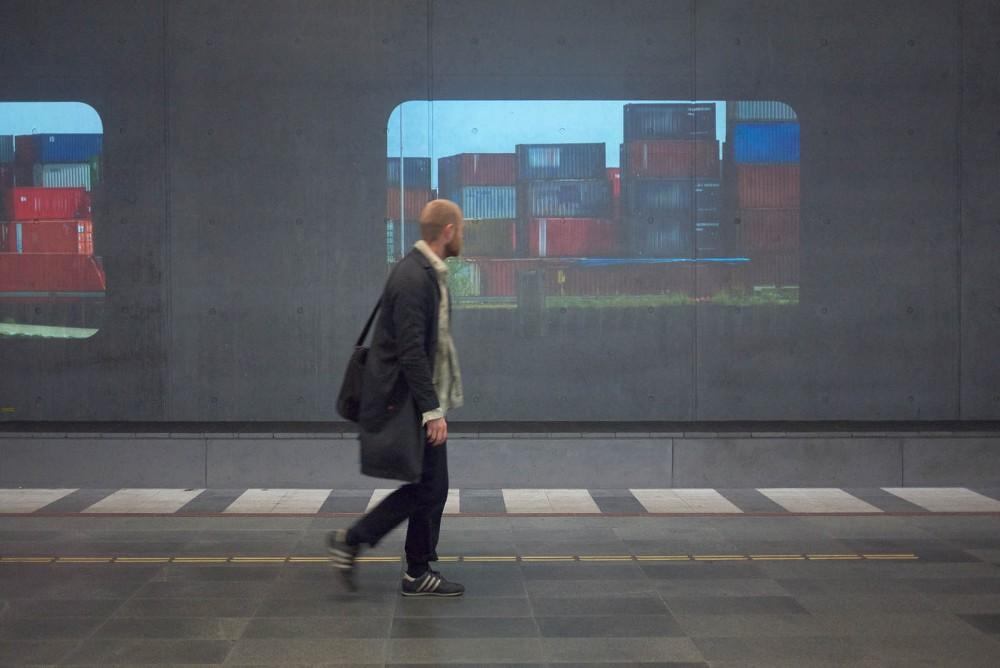 En man går på perrongen och tittar på en projektion av färgade containrar som ligger staplade på varandra. Tania Ruiz Gutiérrez, Annorstädes