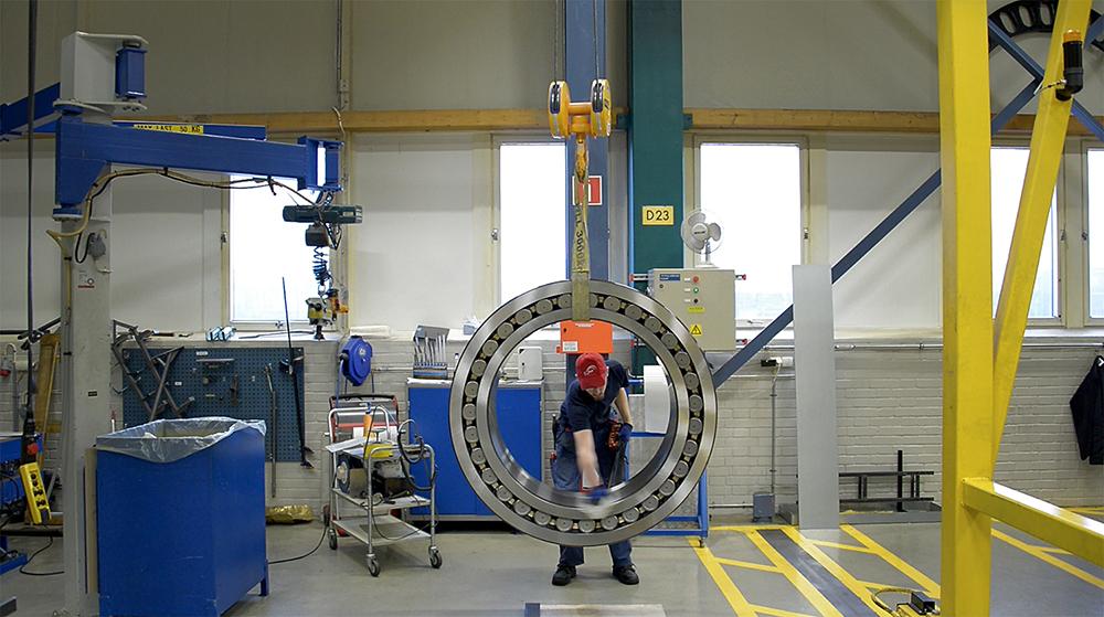 En man rengör ett stort stålhjul som hänger i en takkran i en industrilokal.