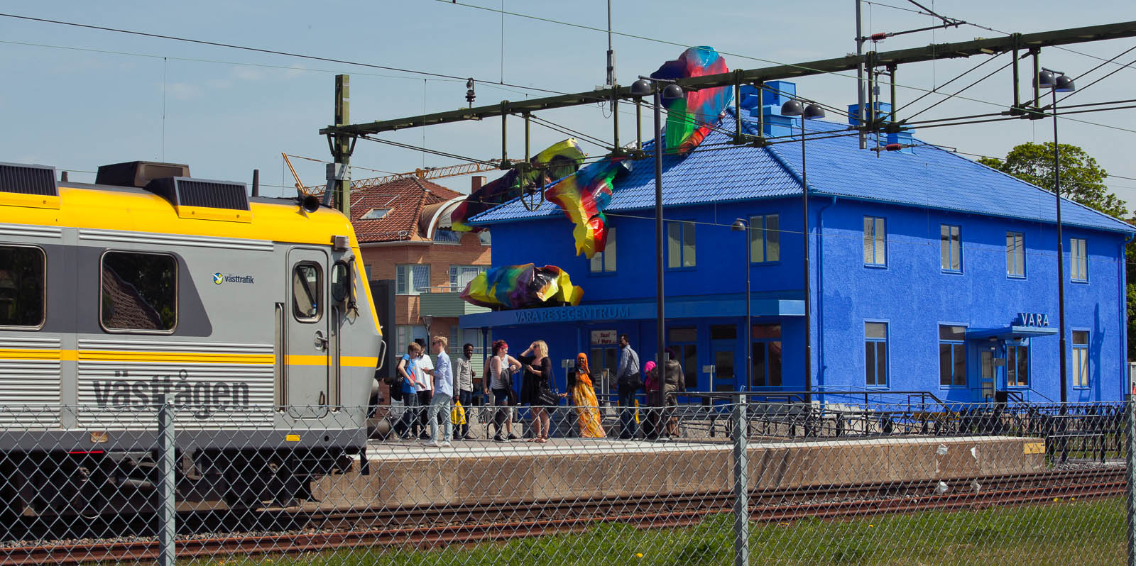 Blåmålade Vara Resecentrum, med färgglada objekt på taket och ett tåg på väg in. Katharina Grosse, Blue Orange, 2012