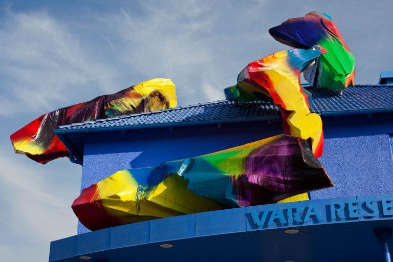 Detalj av blåmålade Vara Resecentrum, med färgglada objekt på taket. Katharina Grosse, Blue Orange, 2012