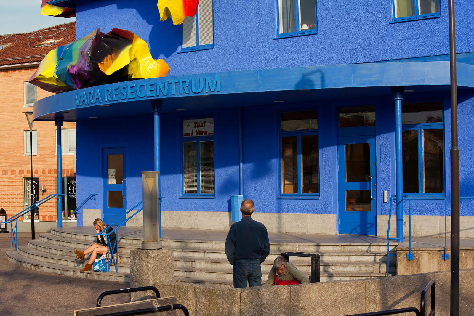 Detalj av blåmålade Vara Resecentrum, med färgglada objekt på taket. Människor som tittar. Katharina Grosse, Blue Orange, 2012