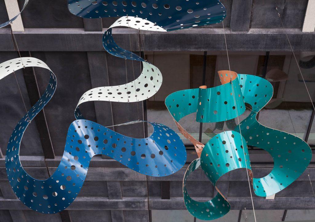 Ett blå och ett turkost veckat och perforerat metallband. I bakgrunden en husfasad. Gunilla Poignant, Bevingad