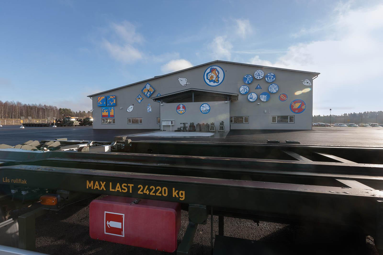 Ett tjugotal skyltar fästa i olika konstellationer på kortändan av en grå byggnad omgiven av parkeringsplats och skog. Anton Wiraeus, Vägledare