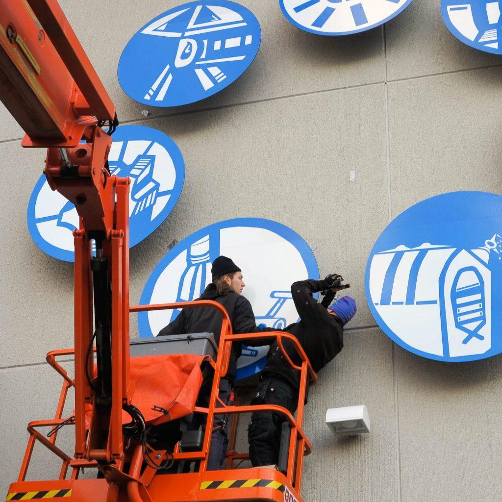 Två män i en skylift i färd med att fästa runda blåvita skyltar på väggen. Anton Wiraeus, Vägledare