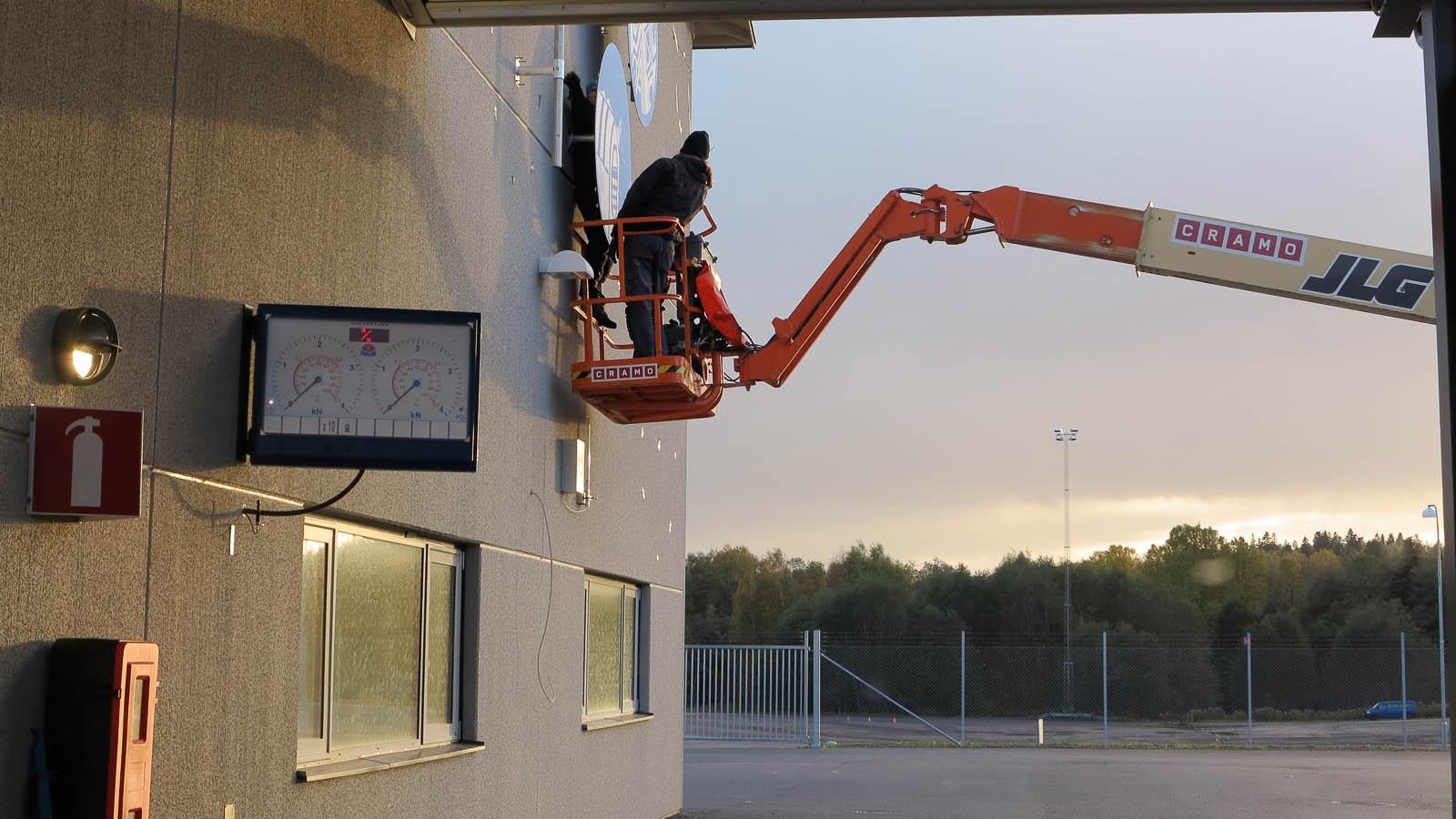Man i skylift fäster en stor skylt på väggen. Anton Wiraeus, Vägledare