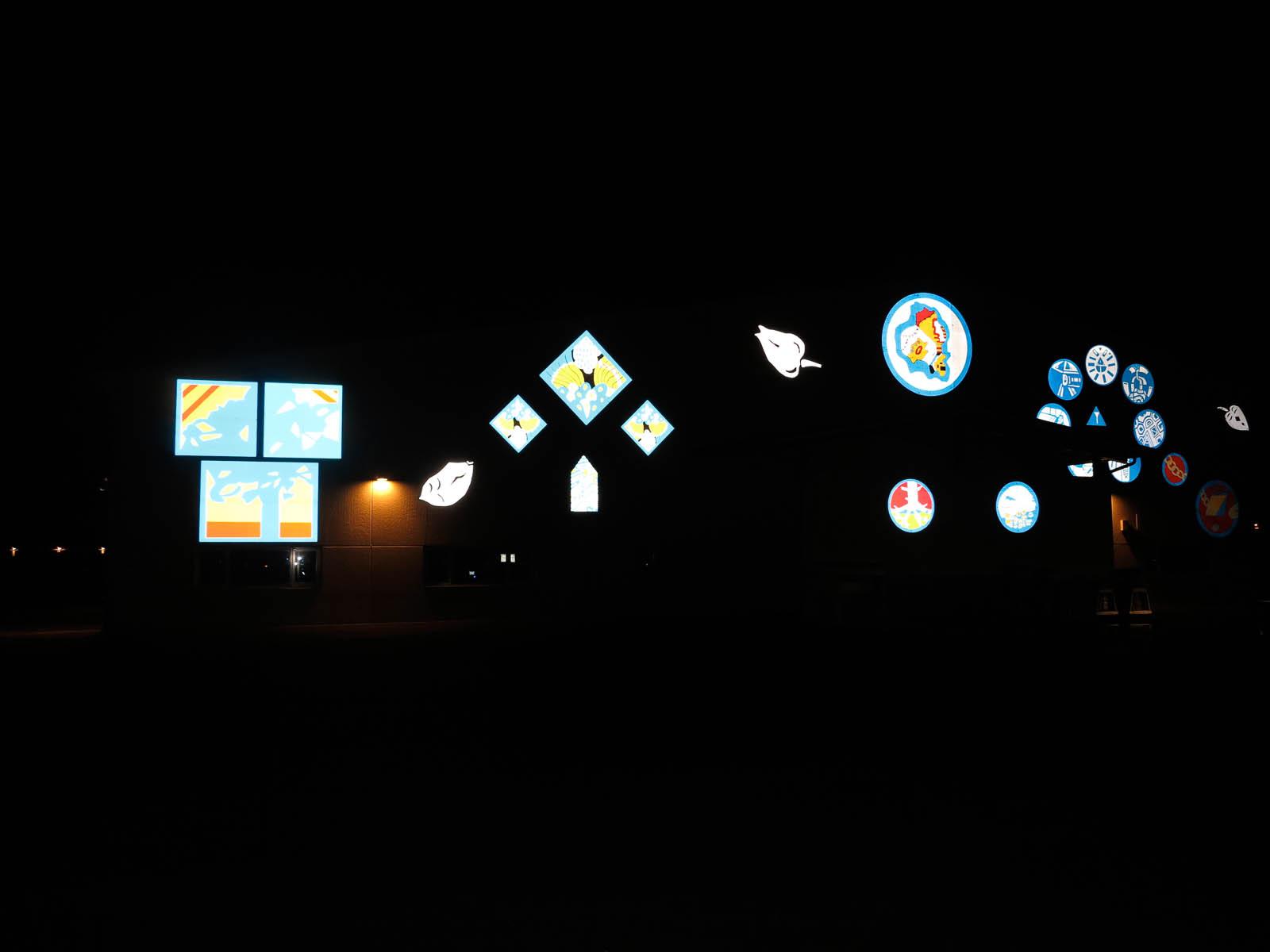 I mörkret syns nästan enbart de ljusreflekterande skyltarna. Anton Wiraeus, Vägledare (2013)