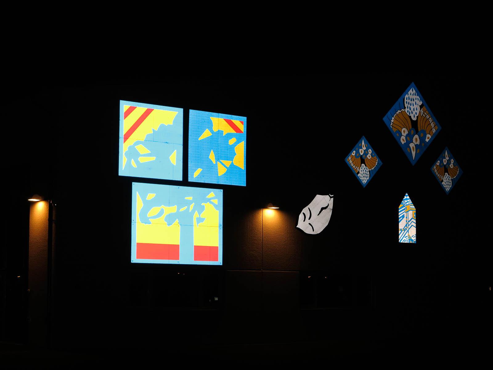 Lysande skyltar i mörkret. Var och en som en rebus som eventuellt kan utläsas. Anton Wiraeus, Vägledare (2013)